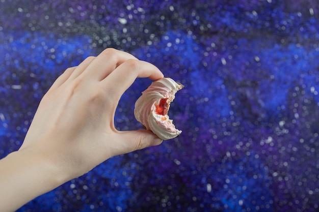 Mão de uma mulher segurando um bolinho delicioso mordido.