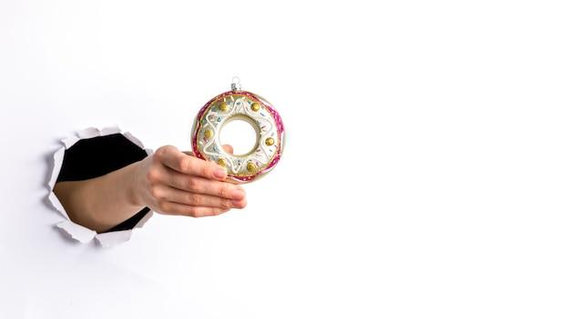 Mão de uma mulher segurando um brinquedo de natal - donut de vidro colorido decorativo através de um buraco redondo rasgado em papel branco. copie o espaço.
