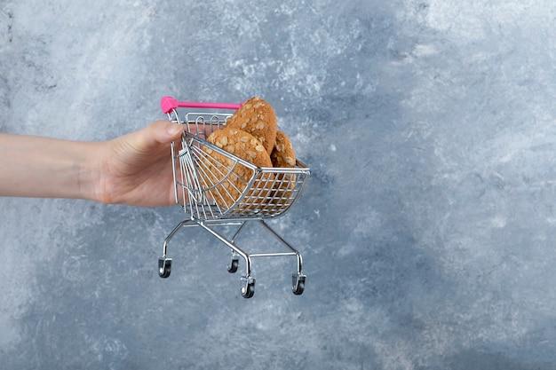 Mão de uma mulher segurando um carrinho pequeno com biscoitos de aveia colocados sobre uma mesa de pedra.