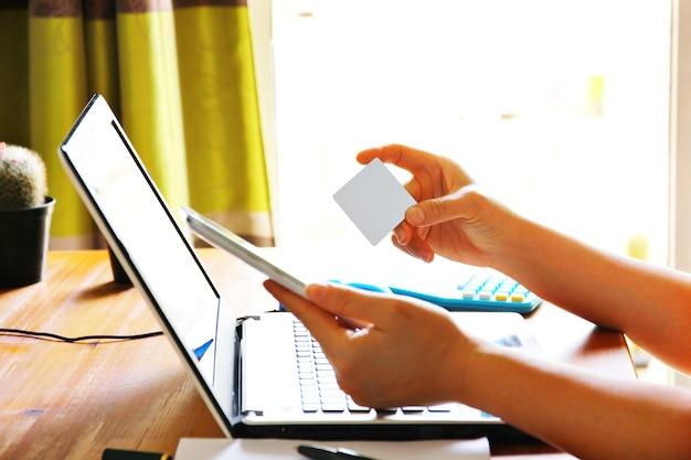 Mão de uma mulher segurando um cartão cinza em branco, pagando enquanto faz compras online