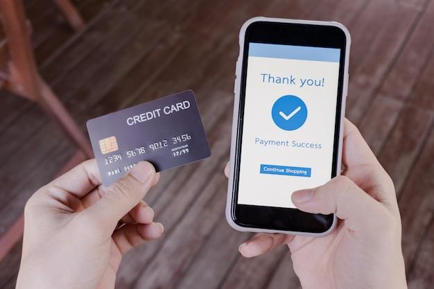 Mão de uma mulher segurando um cartão de crédito e um smartphone com um texto de agradecimento após o pagamento online