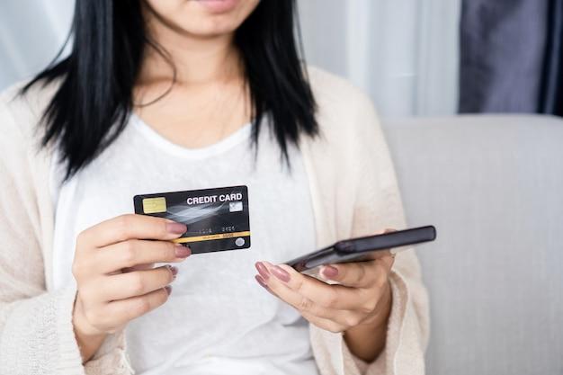 Mão de uma mulher segurando um cartão de crédito e um smartphone, pagando compras online