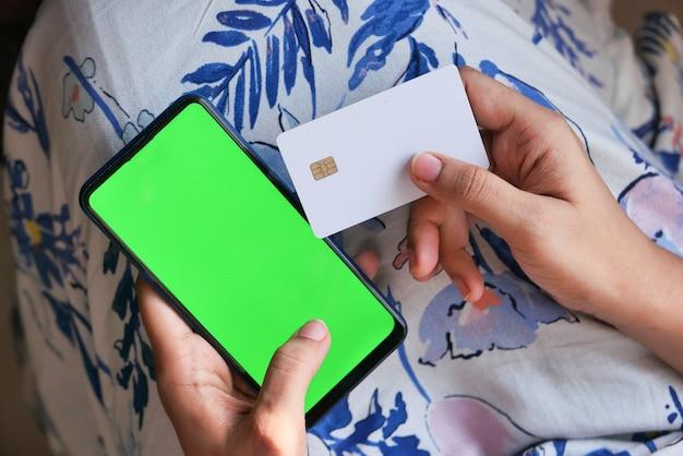 Mão de uma mulher segurando um cartão de crédito e usando o smartphone para fazer compras online
