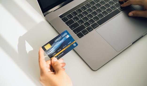 Mão de uma mulher segurando um cartão de crédito e usando um laptop para fazer compras online em uma mesa branca.