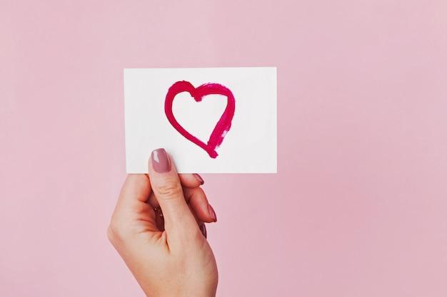Mão de uma mulher segurando um cartão de papel com o símbolo do coração desenhado nele com um batom vermelho