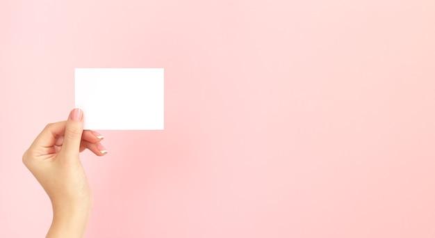 Mão de uma mulher segurando um cartão de visita branco em branco, desconto ou folheto sobre fundo rosa