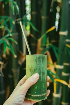 Mão de uma mulher segurando um copo artesanal com madeira de bambu. recipientes naturais. reutilize e recicle copos orgânicos.