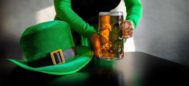 Mão de uma mulher segurando um copo de cerveja perto do chapéu do dia de são patrício de um duende no preto