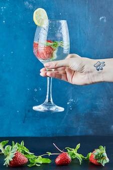 Mão de uma mulher segurando um copo de suco com frutas inteiras e hortelã dentro