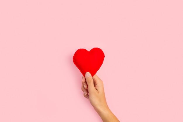 Mão de uma mulher segurando um coração de tecido vermelho em um fundo rosa com espaço de cópia