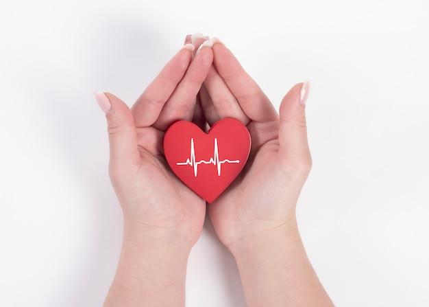 Mão de uma mulher segurando um coração vermelho, batimentos cardíacos. conceito de saúde