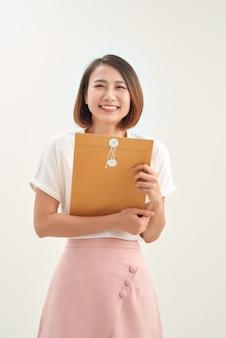 Mão de uma mulher segurando um envelope pardo em fundo branco