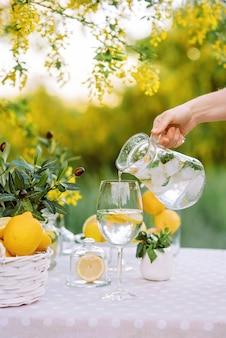 Mão de uma mulher segurando um frasco de vidro de mojito e despejando-o no copo