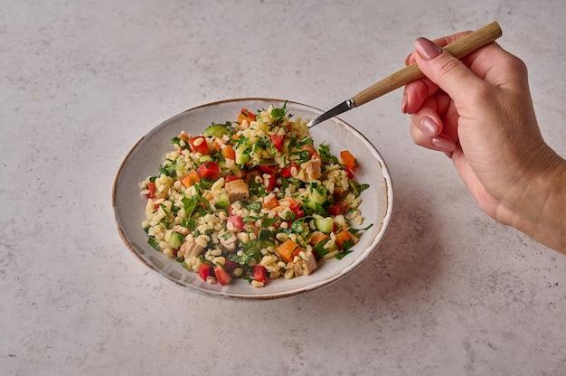 Mão de uma mulher segurando um garfo com salada tabule na tigela sobre fundo claro