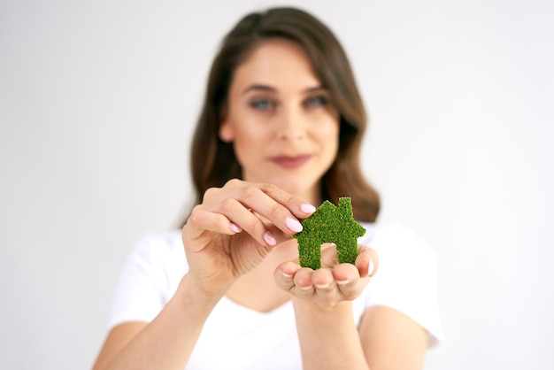 Mão de uma mulher segurando um ícone de casa ecológica