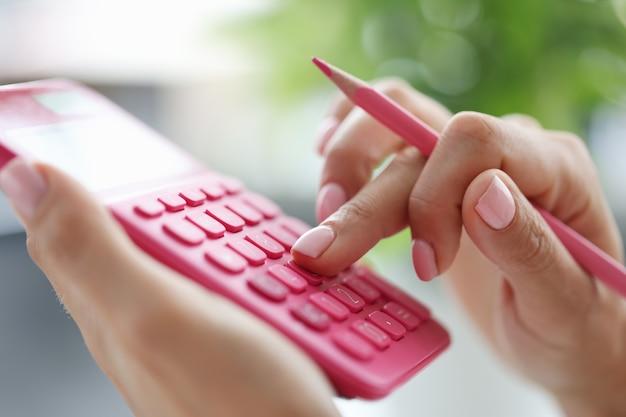 Mão de uma mulher segurando um lápis rosa e contando com o conceito de contabilidade doméstica do close up da calculadora