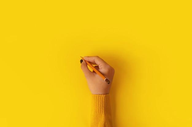 Mão de uma mulher segurando um lápis sobre fundo amarelo