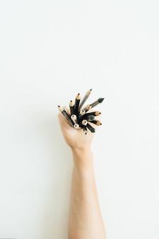 Mão de uma mulher segurando um monte de lápis na superfície branca