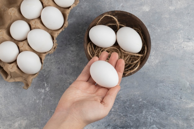 Mão de uma mulher segurando um ovo de galinha branco fresco sobre um fundo de mármore.