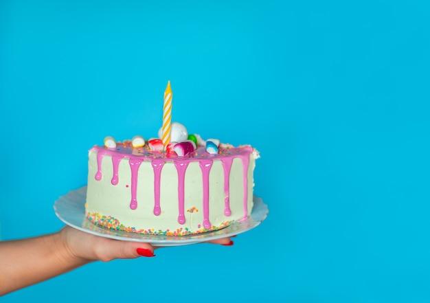 Mão de uma mulher segurando um pedaço de bolo de aniversário em fundo azul, com espaço de cópia