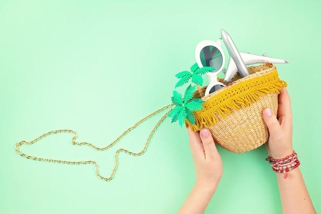 Mão de uma mulher segurando um saco de palha com acessórios de férias de verão. férias de verão, viagens para países tropicais, litoral, conceito de estilo de verão. vista superior, configuração plana