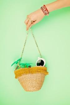 Mão de uma mulher segurando um saco de palha com acessórios de férias de verão. férias de verão, viagens para países tropicais, litoral, conceito de estilo de verão.