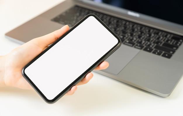 Mão de uma mulher segurando um smartphone e a tela está em branco, conceito de rede social