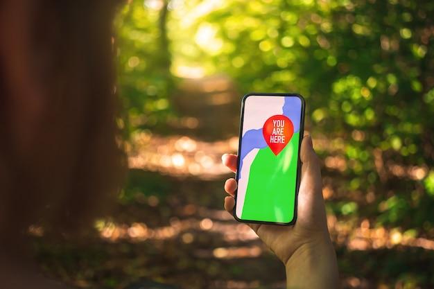 Mão de uma mulher segurando um telefone celular com o mapa na floresta, navegação ao ar livre com smartphone moderno, foto do conceito de atividade turística
