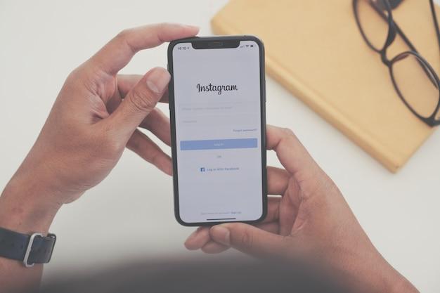 Mão de uma mulher segurando um telefone com serviço de rede social