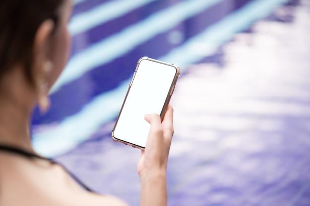 Mão de uma mulher segurando um telefone móvel com maquete de tela branca em branco à beira da piscina.