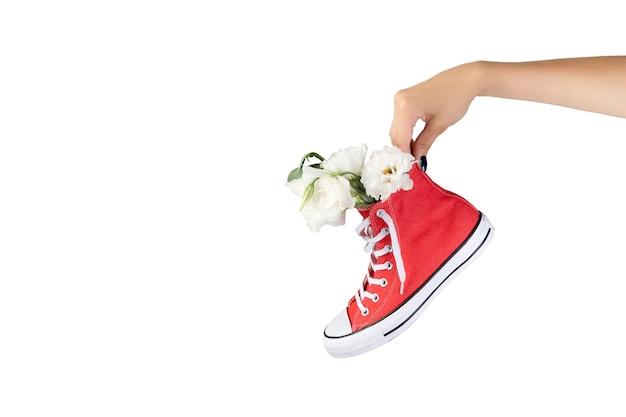 Mão de uma mulher segurando um tênis vermelho da moda com flores
