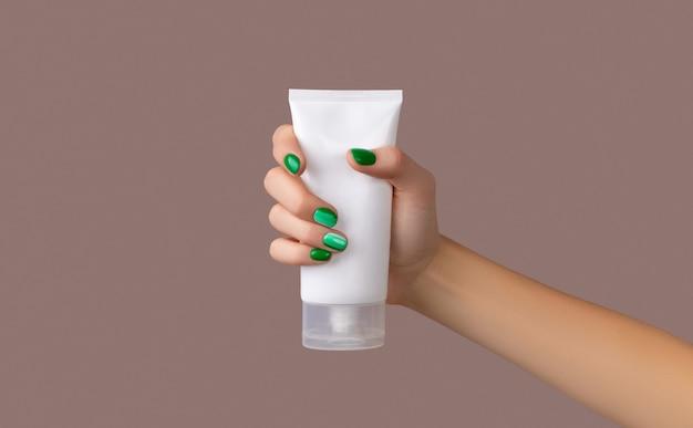Mão de uma mulher segurando um tubo branco em fundo marrom de begie