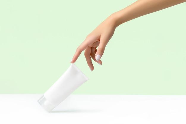 Mão de uma mulher segurando um tubo branco em verde pastel