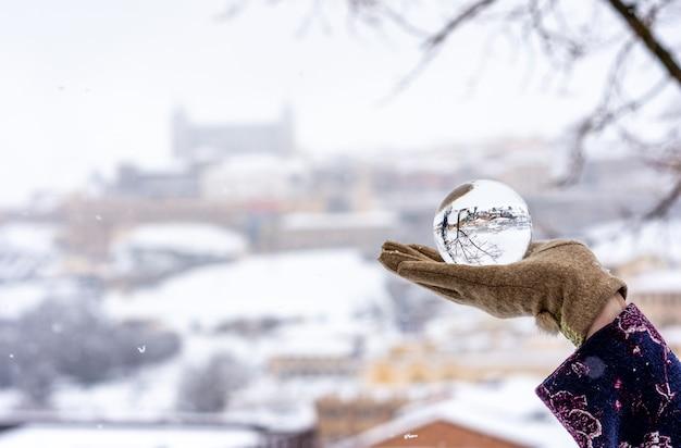 Mão de uma mulher segurando uma bola de cristal em uma paisagem urbana de neve.