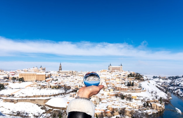 Mão de uma mulher segurando uma bola de cristal. vista panorâmica nevada da cidade de toledo ao fundo.