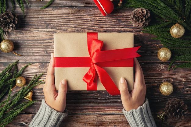 Mão de uma mulher segurando uma caixa de presente com fita vermelha no chão de madeira