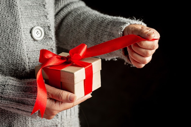 Mão de uma mulher segurando uma caixa de presente com fita vermelha