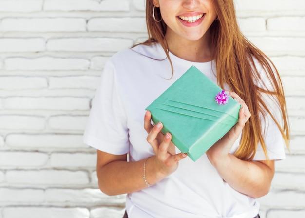Mão de uma mulher segurando uma caixa de presente verde