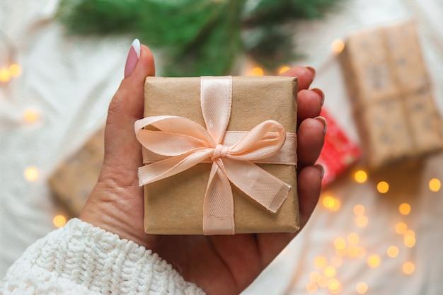 Mão de uma mulher segurando uma caixa de presente