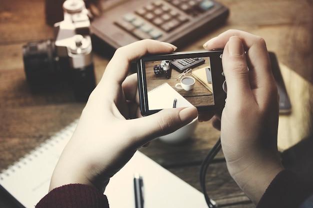 Mão de uma mulher segurando uma câmera digital na mesa de trabalho