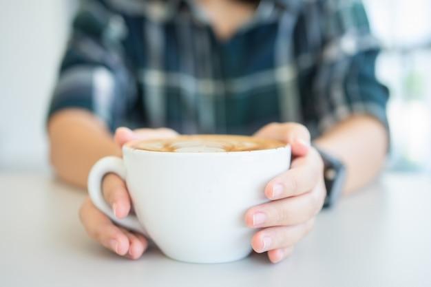 Mão de uma mulher segurando uma caneca de café branco. o café é um café com leite.