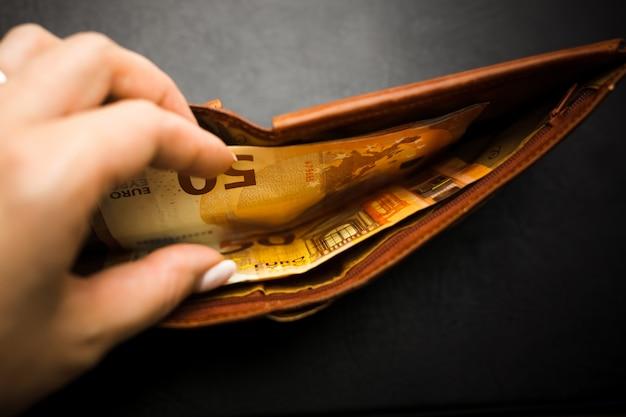 Mão de uma mulher segurando uma carteira preta com dinheiro do euro.
