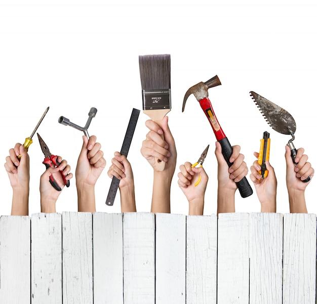 Mão de uma mulher segurando uma coleção de ferramentas diy conjunto com branco de madeira isolado no branco