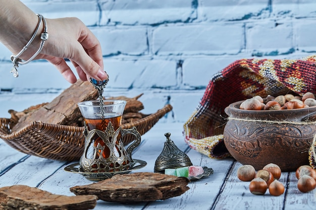 Mão de uma mulher segurando uma colher de chá e vários doces na mesa de madeira azul