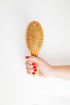 Mão de uma mulher segurando uma escova de cabelo de madeira