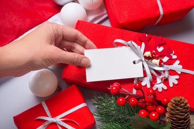 Mão de uma mulher segurando uma etiqueta de papelão branco, etiqueta na caixa embrulhada para presente