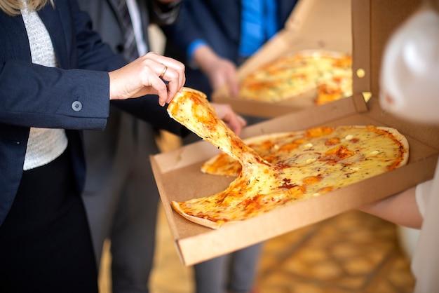 Mão de uma mulher segurando uma fatia de pizza da caixa
