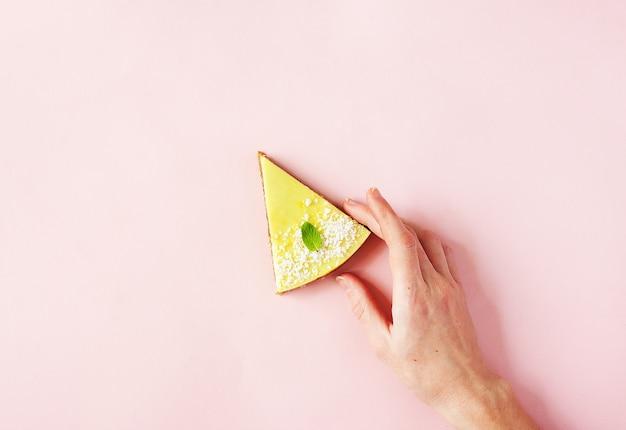 Mão de uma mulher segurando uma fatia de sobremesa saudável crua na rosa