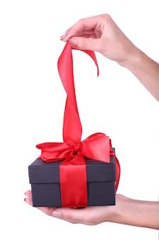 Mão de uma mulher segurando uma fita e abrindo a caixa de presente isolada no branco