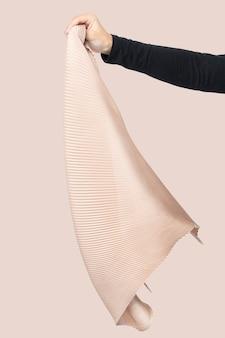 Mão de uma mulher segurando uma foto de estúdio de moda com cachecol pregueado bege